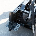 Snow blower safety step for skid steer entry